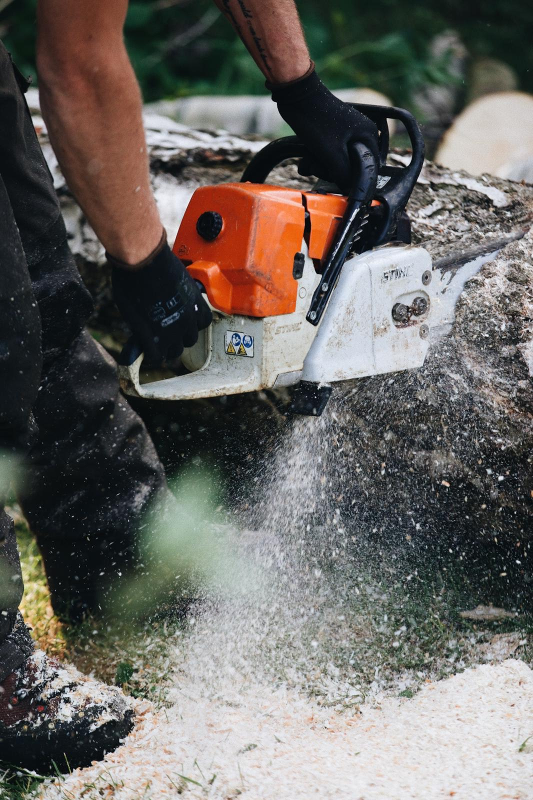 a man cutting using chainsaw